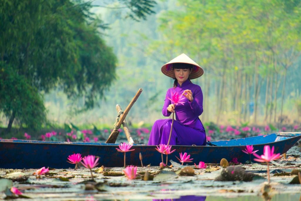Dívka na loďce cestou k Voňavé pagodě (Chua Huong)
