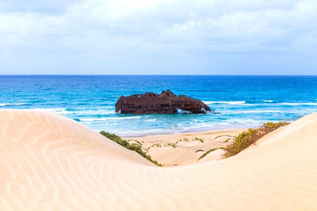 Písečné duny a vrak lodi v moři na ostrově Boa Vista